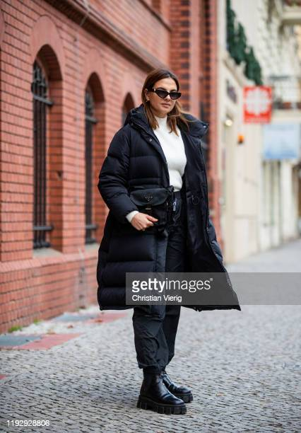 Anna Winter is seen wearing Valentino sunglasses, black puffer jacket &Other Stories, creme white knit Pepe Jeans, black Weekday pants, Prada bag and...