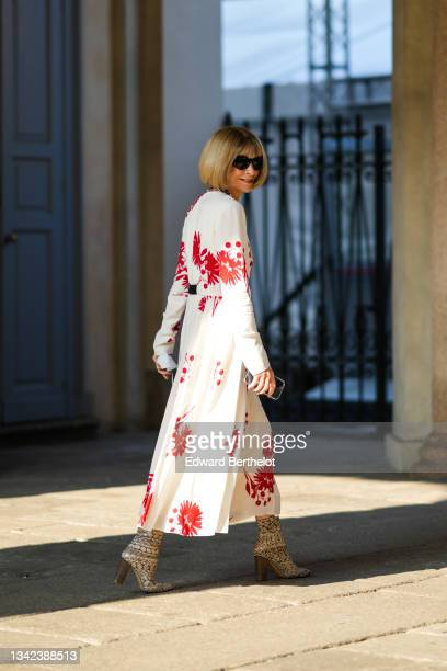 Anna Wintour wears black sunglasses from Chanel, a gold and silver chain necklace, a white with flower print pattern long sleeves / belted / flowing...