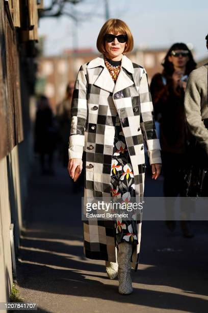 Anna Wintour wears sunglasses, a bejeweled necklace, a black and white checkered long trench coat, a floral print dress, boots, outside Marni, during...