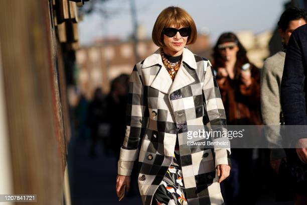 Anna Wintour wears sunglasses, a bejeweled necklace, a black and white checkered long trench coat, a floral print dress, outside Marni, during Milan...