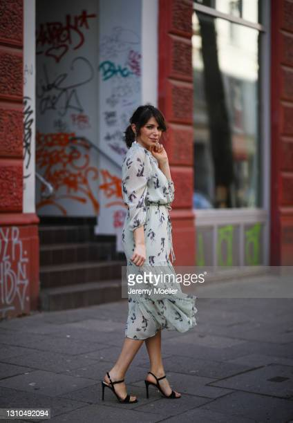 Anna Wolfers poses wearing light green midi dress and black heels on March 30, 2021 in Hamburg, Germany.