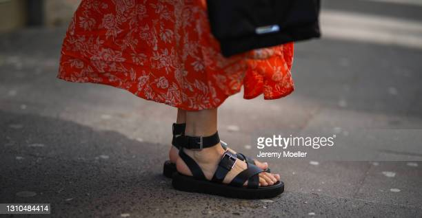 Anna Wolfers poses wearing red floral midi dress, black bag and black open toe sandals on March 30, 2021 in Hamburg, Germany.