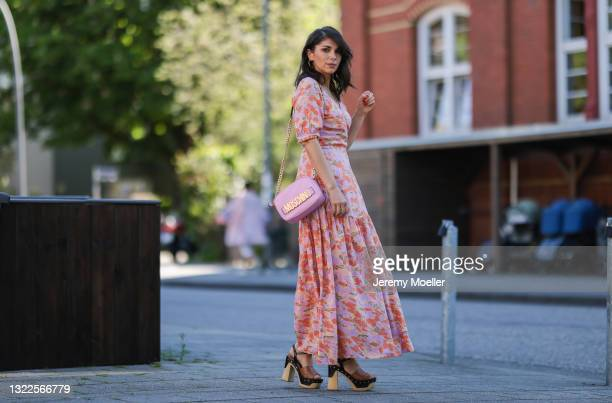 Anna Wolfers wearing colorful wrap dress via Goldig Shop, pink Moschino leather bag and brown heeled clogs on May 31, 2021 in Hamburg, Germany.