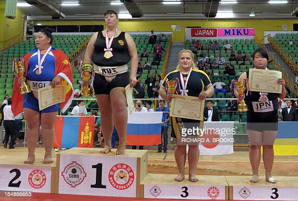 Anna Zhigalova of Russia poses with the winner's trophy on the podium following her victory in the women's heavyweight competition at the 18th Sumo...