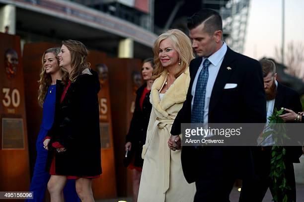 Annabel Bowlen holds the hand of son John as they walk with family before the unveiling of Pat Bowlen's bust in front of Sports Authority Field at...