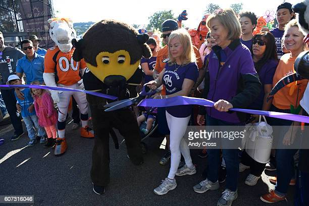 Annabel Bowlen surrounded by family friends and mascots cuts the ribbon to begin the 27th annual Denver Walk to End Alzheimer's at City Park...