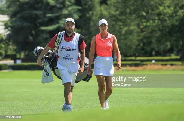 Annabel Dimmock of England prepares to play her second shot on the first hole with her caddie Daniel Torrance the son of the former European Ryder...