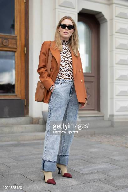 Annabel Rosendahl is seen on the street during Fashion Week Stockholm wearing a copper blazer with animal print shirt and washed jeans on August 28...
