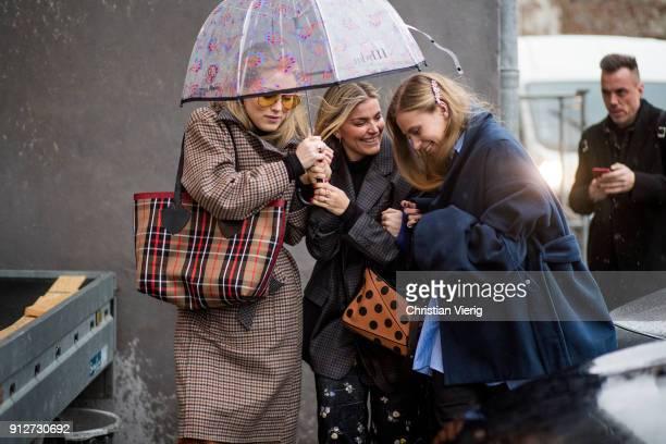Annabel Rosendahl Janka Polliani Tine Andrea fighting the rain under an umbrella outside J Lindeberg during the Copenhagen Fashion Week Autumn/Winter...