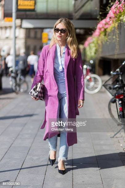 Annabel Rosendahl wearing a pink wool coat checked clutch denim jeans Dior slingbacks outside Whyred on August 30 2017 in Stockholm Sweden