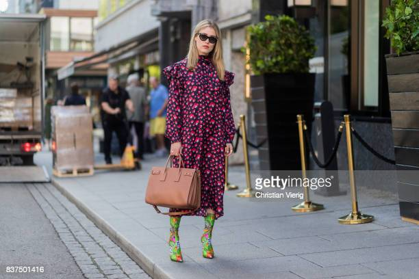 Annabel Rosendahl wearing a red dress, sock boots with floral print outside byTiMo on August 22, 2017 in Oslo, Norway.