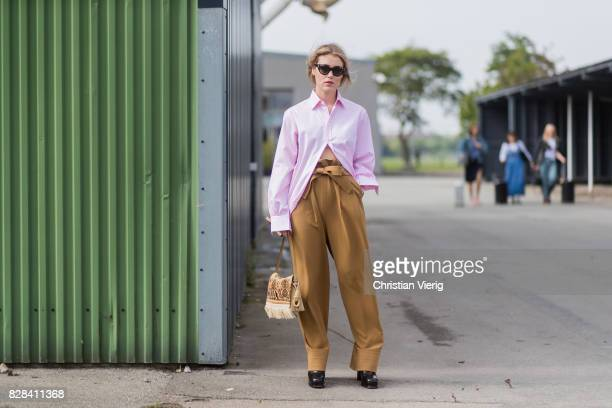 Annabel Rosendahl wearing high waisted brown pants, pink button shirt outside By Malene Birger on August 09, 2017 in Copenhagen, Denmark.
