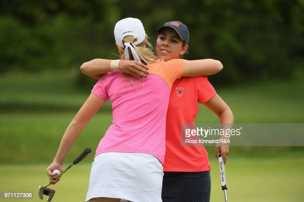 Annabell Fuller of the Great Britain and Ireland team and Kristen Gillman of the United States team embrace on the 14th green during the singles...