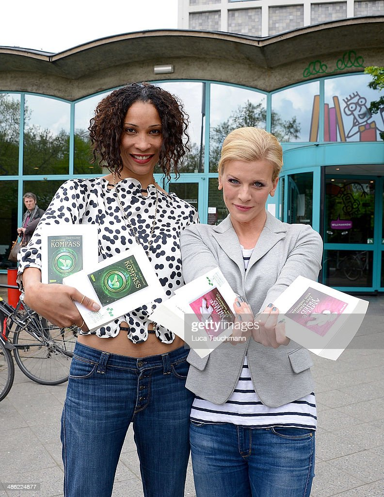 Annabelle Mandeng and Eva Habermann pose with books as they give away books during World Book Day on April 23, 2014 in Berlin, Germany.
