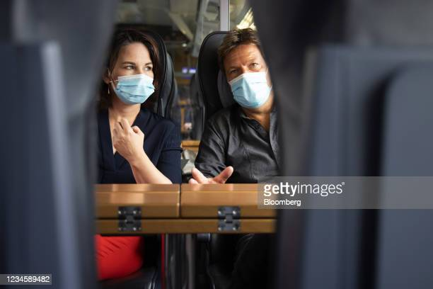 Annalena Baerbock, chancellor candidate for the Green Party, left, and Robert Habeck, co-leader of the Green Party, travel on a train from Berlin to...