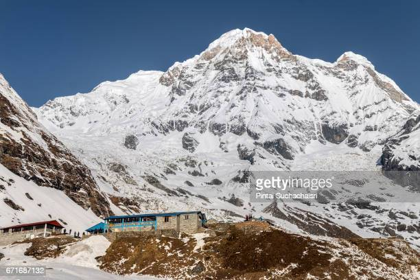annapurna base camp and snow covered annapurna south peak, nepal - annapurna south stock photos and pictures