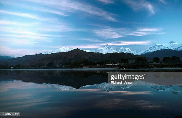 Annapurna Himal reflected in Phewa Lake at sunrise.