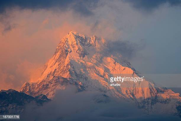 annapurna mountain peak glowing in first morning light - annapurna conservation area stock photos and pictures
