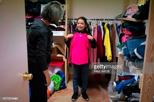 Annarut Hernandez from Honduras looks for clothes with volunteer Guadalupe Gallardo at the church hall of the Basilica of San Albino in Mesilla New...