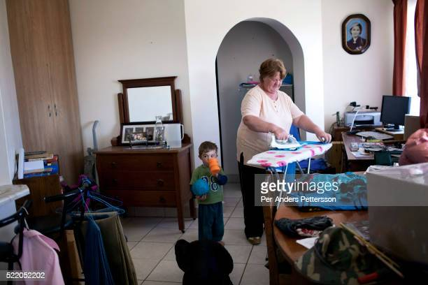 Annatjie Oncke irons clothes as she works as a domestic worker for a big family with children on July 15 2013 in Kleinfontein outside Pretoria South...