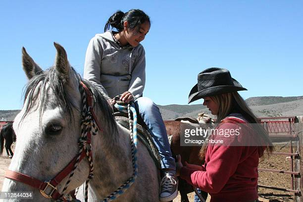 Anndi Snyder right adjusts stirrups for a girl on a class trip from a school on the Navajo reservation in Utah