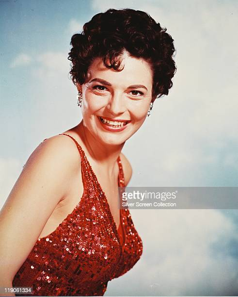 Anne Bancroft US actress smiling and wearing a red sequinned halterneck top circa 1955