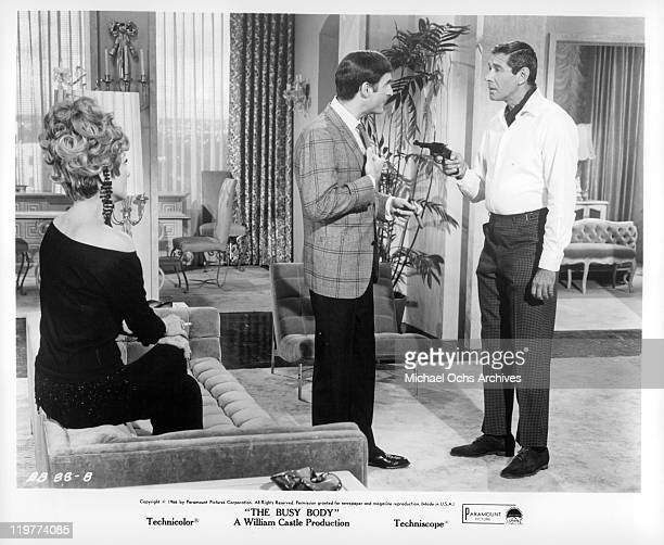 Anne Baxter sits while Sid Caesar has gun pointed at him by Jan Murray in a scene from the film 'The Busy Body' 1966