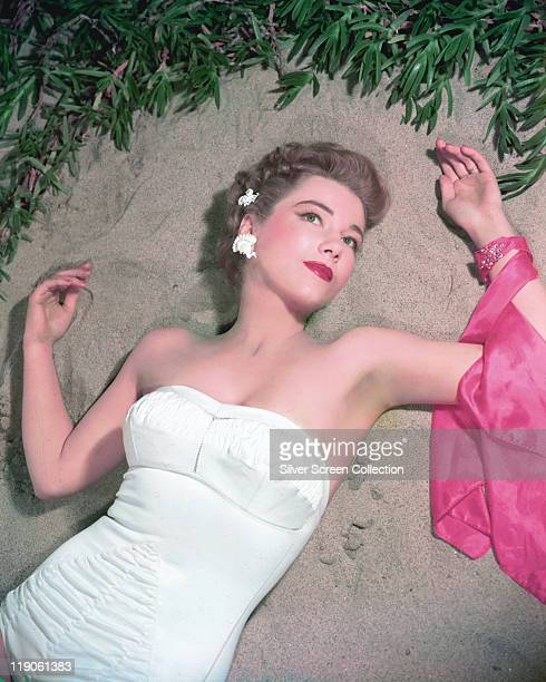 Anne Baxter US actress reclining on sand and wearing a white swimsuit circa 1945