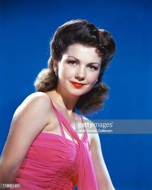 Anne Baxter US actress wearing a pink halterneck top in a studio portrait against a blue background circa 1945