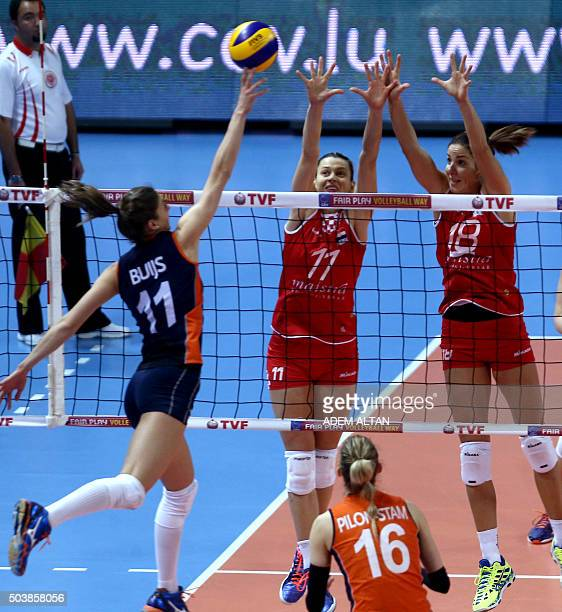 Anne Bujs of The Netherlands jumps for the ball against K Barun Susnjar and Maca Poljak of Croata during their European Olympic Qualification...