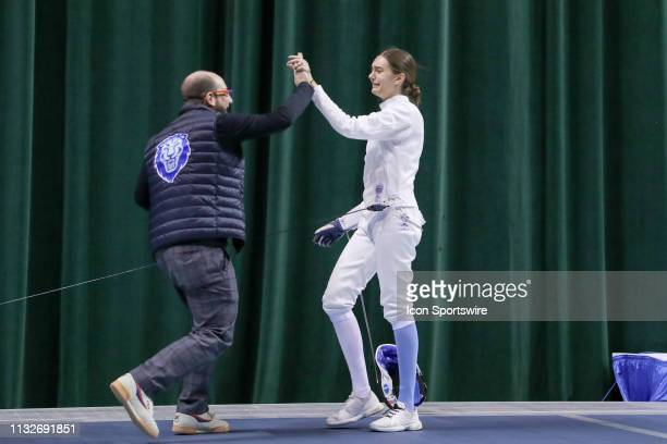 Anne Cebula of Columbia gets a highfive from Columbia head coach Michael Aufrichtig after winning the championship in Women's Epee at the National...
