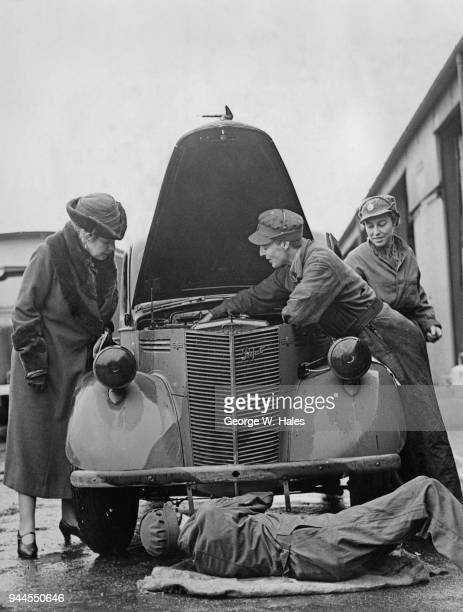Anne Chamberlain the wife of British Prime Minister Neville Chamberlain watches members of the ATS at work on a vehicle during a visit to the Field...