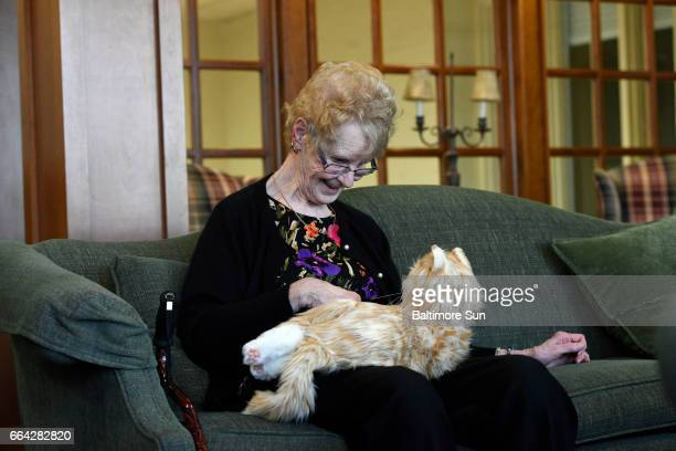 Anne Dongarra a resident at Glen Meadows Retirement Community pets 'Henry' a robotic companion cat that responds to petting and motion
