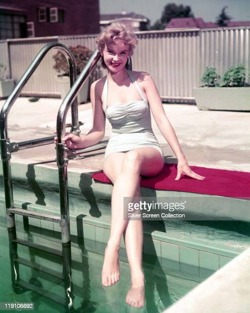 Anne Francis US actress wearing a swimsuit while posing on the edge of a swimming pool beside the pool ladder with her feet in the water circa 1960