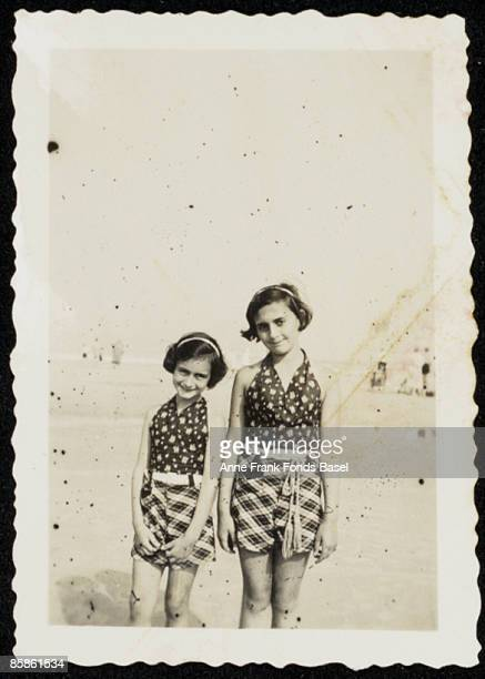 Anne Frank and her sister Margot standing on a beach circa 1935