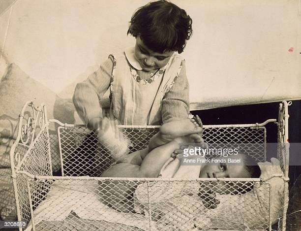 Anne Frank getting her buttocks powdered in a crib by her sister Margot Frank Frankfurt am Main Germany From Anne Frank's photo album