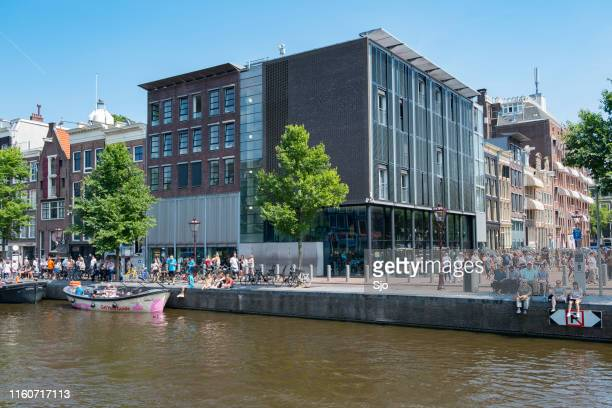 anne frank house and museum in amsterdam with tourists in front of the building - anne frank photos stock pictures, royalty-free photos & images