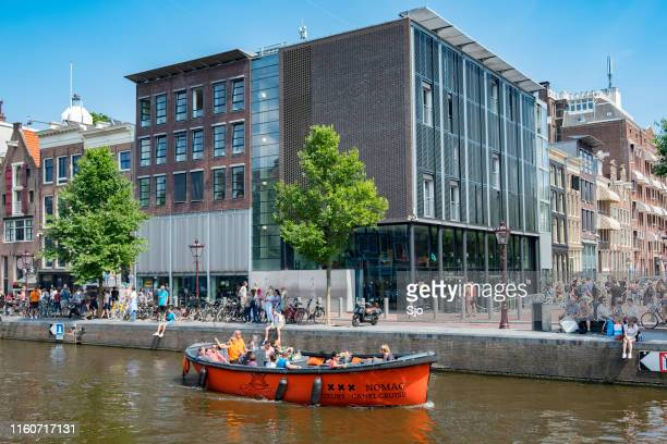 anne frank house and museum in amsterdam with tourists in front of the building - anne frank imagens e fotografias de stock