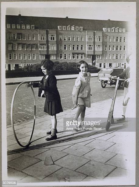 Anne Frank playing on a sidewalk with her friend Sanne Ledermann who is holding a hoop and another child riding a scooter Merwedeplein Amsterdam...