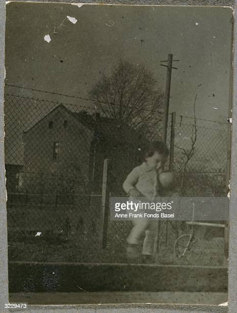 Anne Frank playing with a ball on a street curb in front of a fence Frankfurt am Main Germany Behind her is a tricycle From Anne Frank's photo album