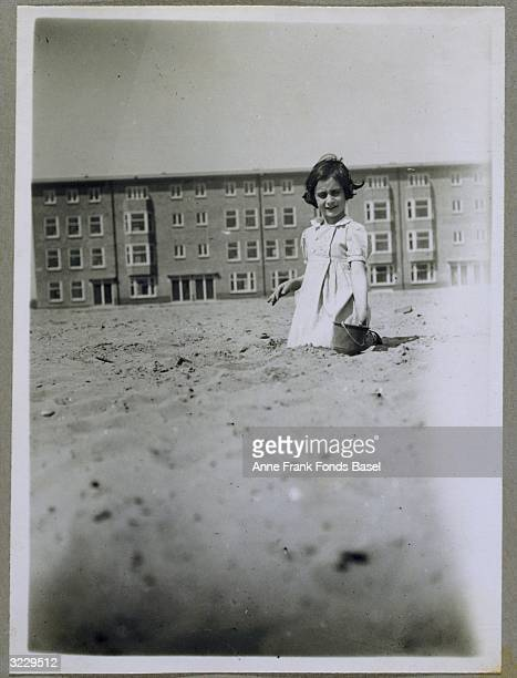 Anne Frank playing with a bucket in the sand at a new building site around Merwedeplein Amsterdam the Netherlands From Anne Frank's photo album