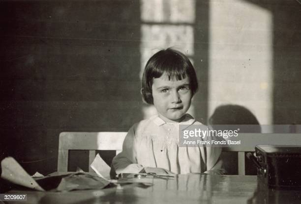Anne Frank sitting at a table in the sunlight This photo was taken from Margot Frank's photo album Frankfurt Germany