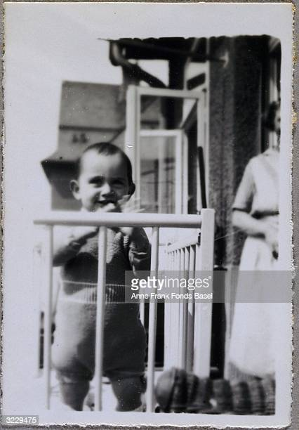 Anne Frank standing in a crib on a balcony as a woman looks on in the background Frankfurt am Main Germany From Anne Frank's photo album