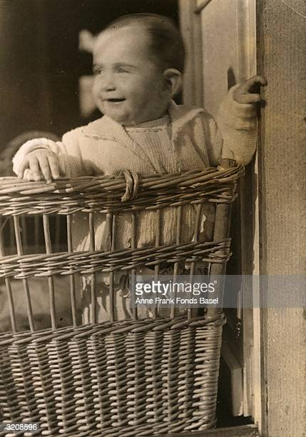 Anne Frank standing in a wicker cradle on a balcony and smiling Frankfurt am Main Germany From Anne Frank's photo album