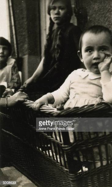 Anne Frank sucking her thumb in a wicker cradle in front of other children on a balcony Frankfurt am Main Germany From Anne Frank's photo album