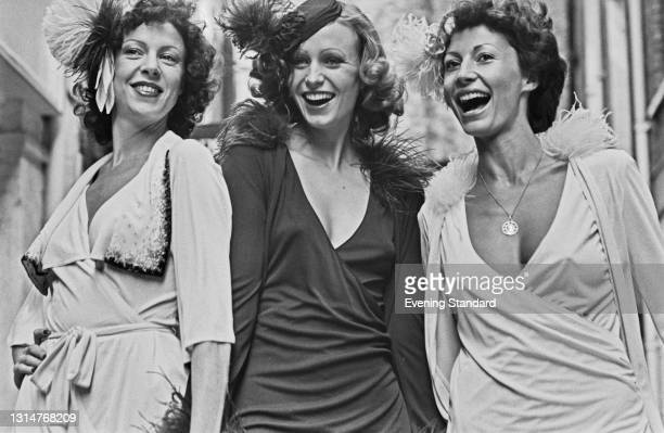 Anne French, Monty and Penny Carter wearing wrap dresses and 20s style hats, UK, 7th August 1974.