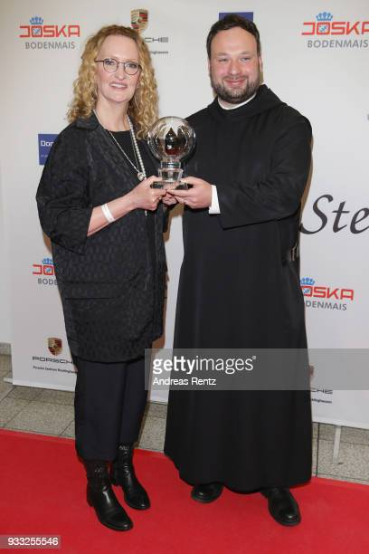 Anne Geddes poses with her award as Father Nikodemus Schnabel smiles during the Steiger Award at Zeche Hansemann on March 17 2018 in Dortmund Germany