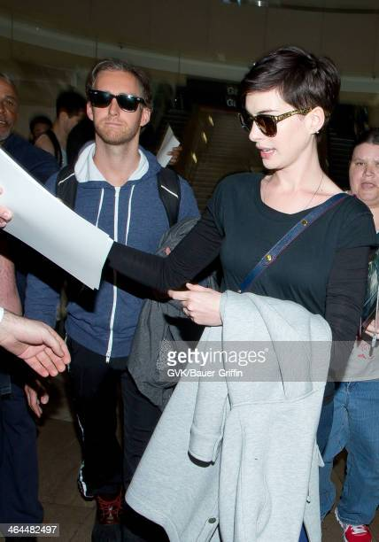 Anne Hathaway and Adam Shulman are seen at Los Angeles International Airport on January 22 2014 in Los Angeles California