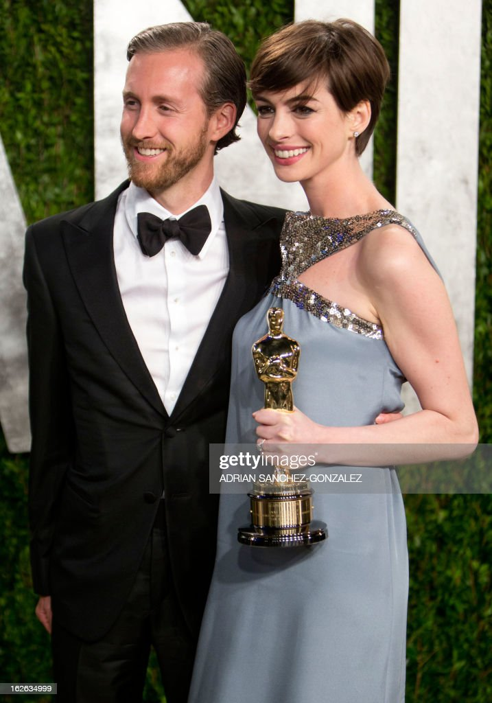 Anne Hathaway carrying her Oscar for best supporting actress and her husband arrive for the 2013 Vanity Fair Oscar Party on February 24, 2013 in Hollywood, California.