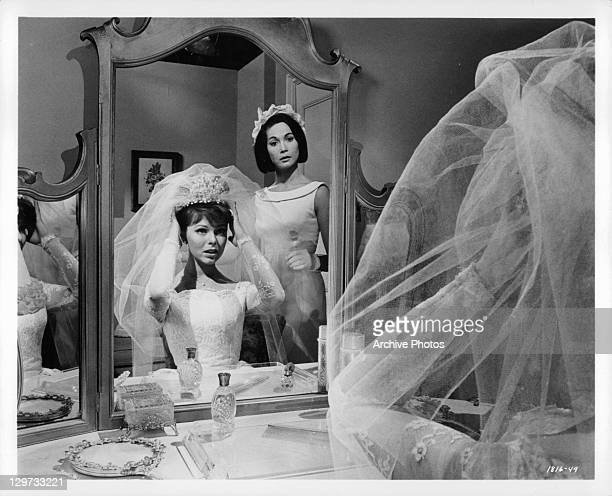 Anne Helm and Nancy Kwan prepare for wedding in a scene from the film 'Honeymoon Hotel' 1964